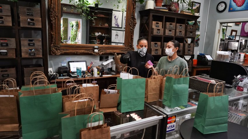 In this Thursday, April 16, 2020, photo, budtenders prepare orders for customers to pick-up at The Higher Path cannabis dispensary in the Sherman Oaks section of Los Angeles.