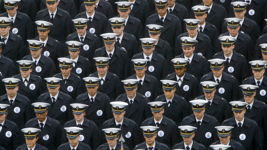 In this Dec. 14, 2019 file photo, Navy midshipmen march onto field ahead of an NCAA college football game between the Army and the Navy in Philadelphia.