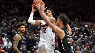 Connecticut's James Bouknight (2) shoots over Cincinnati's Zach Harvey, right, as Cincinnati's Jarron Cumberland, left, looks on in the second half of an NCAA college basketball game, Sunday, Feb. 9, 2020, in Storrs, Connecticut.