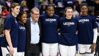 Connecticut seniors Kyla Irwin (25), Crystal Dangerfield (5), Evelyn Adebayo (14), Molly Bent (10), and Batouly Camara (32), stand with Connecticut head coach Geno Auriemma as they were honored before the NCAA college basketball game against Central Florida Saturday, Feb. 22, 2020, in Storrs, Connecticut.