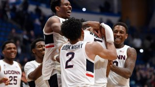 Connecticut's Christian Vital, top left, Connecticut's James Bouknight, front center, and Connecticut's Brendan Adams, back right, congratulate Connecticut's Isaiah Whaley at the end of an NCAA college basketball game against Central Florida, Wednesday, Feb. 26, 2020, in Hartford, Connecticut.