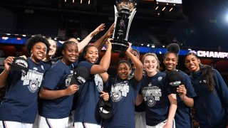Connecticut players hold up the American Athletic Conference championship trophy the end of an NCAA college basketball game against Cincinnati in the American Athletic Conference tournament finals at Mohegan Sun Arena, Monday, March 9, 2020, in Uncasville, Connecticut.