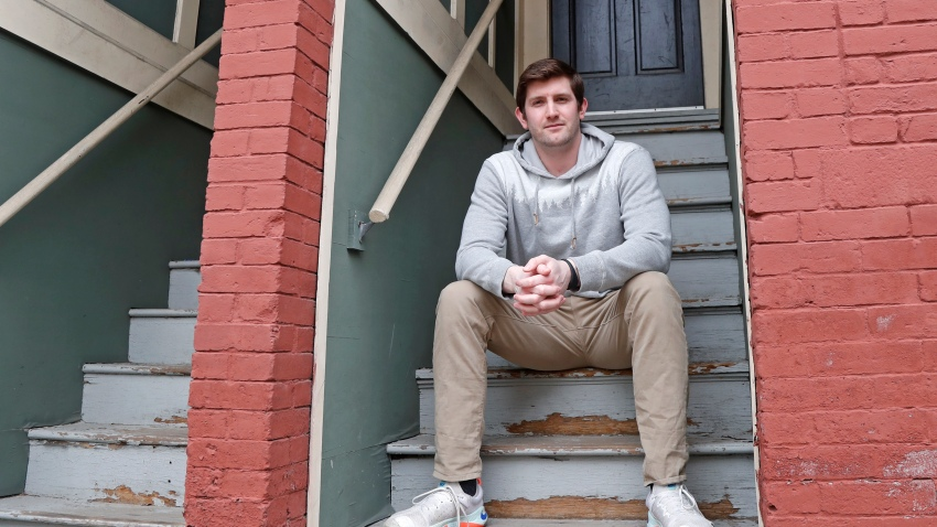 "Cameron Karosis, 27, a software salesman, poses for a portrait outside his home, Tuesday, April 14, 2020, in Cambridge, Mass. Karosis usually strives to protect his personal information. But a scary bout with COVID-19 that began with headaches and fevers, progressed to breathing problems and led to a hospital visit has now left him eager to disclose as much as possible to help halt the virus' spread. ""I'm sick and I'm under a quarantine -- hold me accountable for it,"" he said. ""You have the potential to kill other people."""