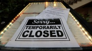 In this April 28, 2020, file photo, a closed sign is posted at a restaurant along the River Walk in San Antonio.