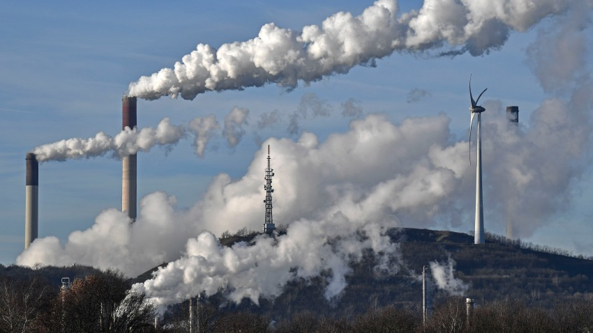 This Jan. 16, 2020 file photo shows a Uniper energy company coal-fired power plant and a BP refinery beside a wind generator in Gelsenkirchen, Germany.