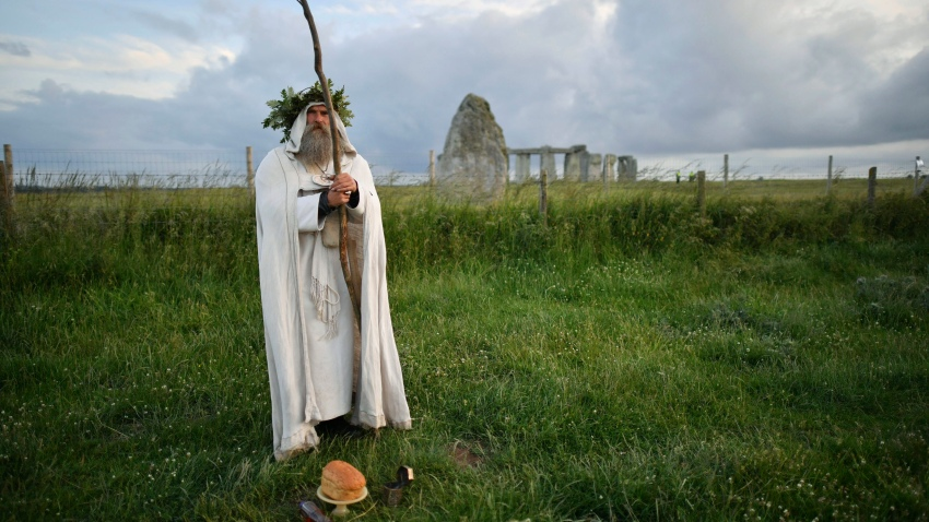 An Archdruid performs a ritual near to the cordoned off Stonehenge as a small group of people gathered to celebrate the Summer Solstice, the longest day of the year, near Salisbury, England, Sunday, June 21, 2020.