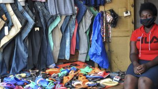 Grace Twisimire, 25, sits in her once-thriving shop selling clothes and plastic shoes in the capital Kampala, Uganda