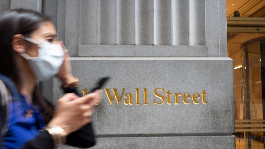 A woman wearing a mask passes a sign for Wall Street, Tuesday, June 30, 2020, during the coronavirus pandemic.