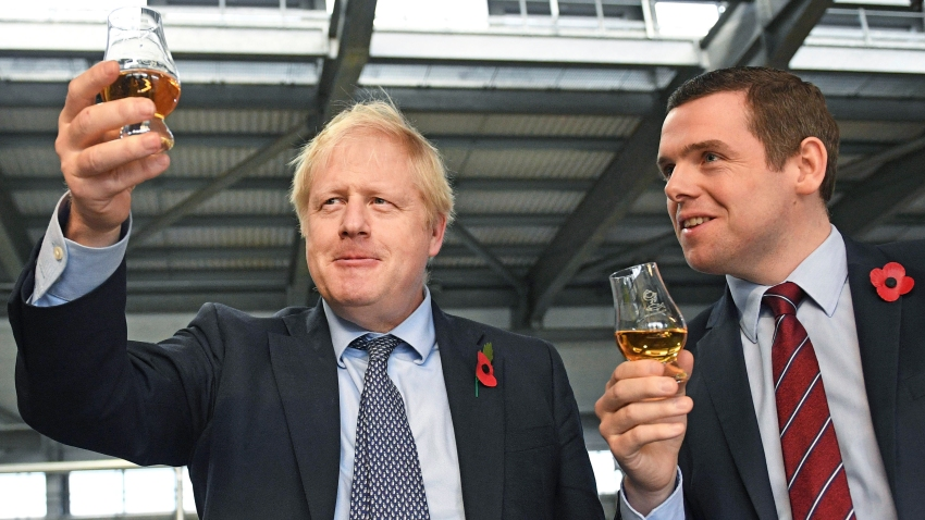In this file photo dated Nov. 7, 2019, showing Britain's Prime Minister Boris Johnson alongside Douglas Ross, parliamentary under-secretary of state for Scotland, right in Moray, Scotland. Junior British government minister Douglas Ross has quit Tuesday May 26, 2020, over Prime Minister Boris Johnson's failure to fire his top aide Dominic Cummings for allegedly breaching COVID-19 coronavirus lockdown rules.