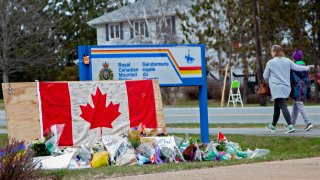 A woman comforts her daughter after they placed flowers at an impromptu memorial in front of the RCMP detachment on April 20, 2020, in Enfield, Nova Scotia, Canada.