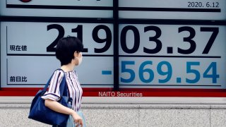 In this June 12, 2020, file photo, a woman looks at an electronic stock board showing Japan's Nikkei 225 index at a securities firm in Tokyo.
