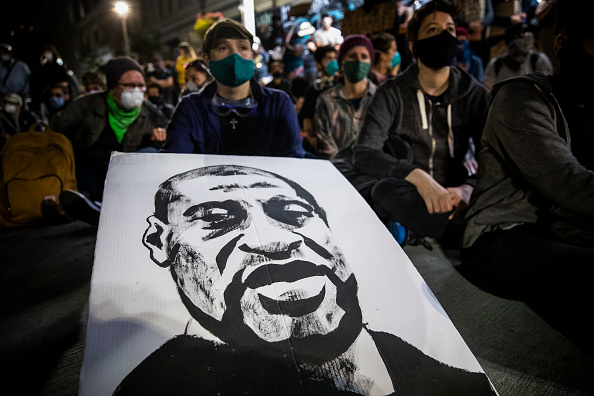 """Demonstrators attend a """"Sit Out the Curfew"""" protest against the death of George Floyd, who died May 25 in Minneapolis while in police custody, along a street in Oakland, California on June 3, 2020."""