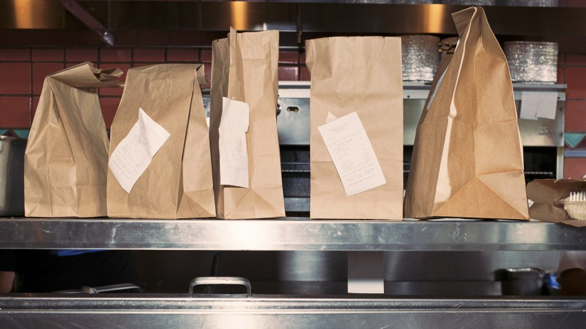 Food in take out bags with receipts, sitting on restaurant shelf