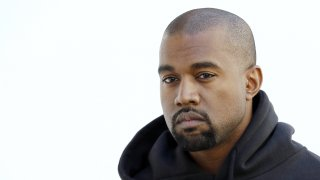 Kanye West poses before Christian Dior 2015-2016 fall/winter ready-to-wear collection fashion show in Paris.