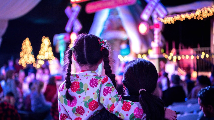 A Mother and child (7 years old) are waiting to see Santa at a Christmas tree lighting ceremony.
