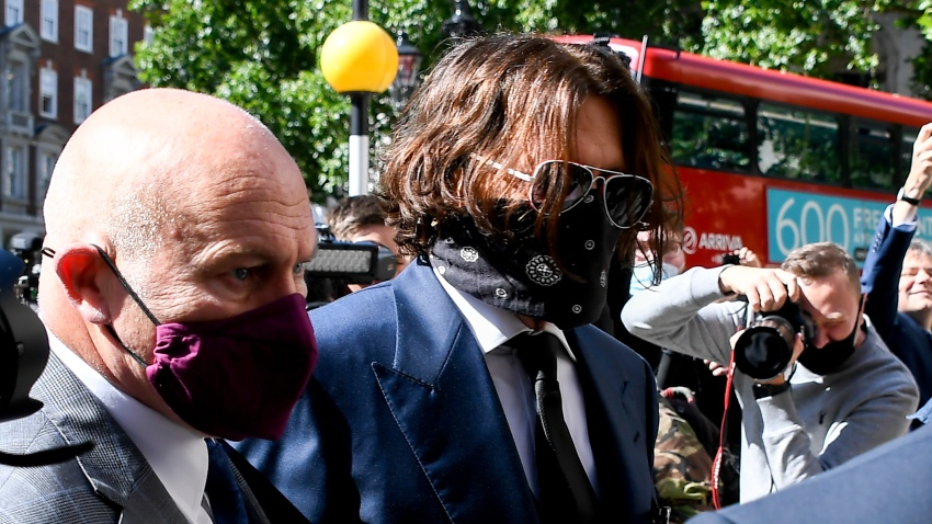 """Johnny Depp, right, wearing a protective mask arrives at the Royal Court of Justice, in London, Tuesday, July 7, 2020. Johnny Depp is suing a tabloid newspaper for libel over an article that branded him a """"wife beater."""""""