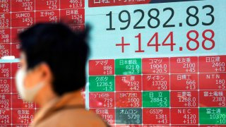 In this April 23, 2020, file photo, a man wearing a mask against the spread of the new coronavirus walks past an electronic stock board showing Japan's Nikkei 225 index at a securities firm in Tokyo.