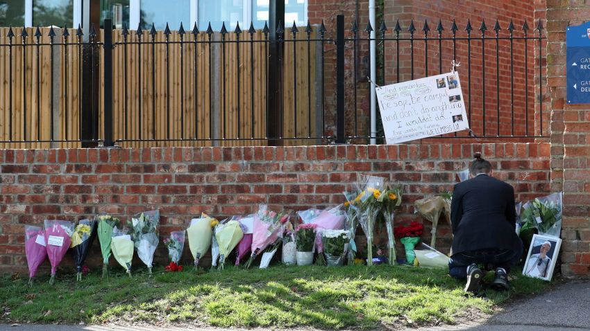 Flower tributes are placed at the entrance to Holt School in Wokingham, England, in memory of teacher James Furlong, a victim of a terror attack in nearby Reading, Monday June 22, 2020. A lone terror suspect remains in custody accused of killing three people and wounding three others in a Reading park on Saturday night.