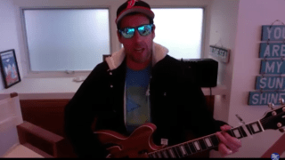 Adam Sandler performs a song on his guitar
