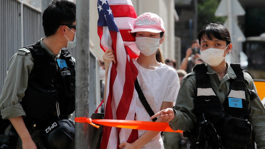"A protester carrying an American flag as she is stopped by riot police during a protest outside the U.S. Consulate in Hong Kong, Saturday, July 4, 2020 to mark the American Independence Day or ""the Fourth of July."""