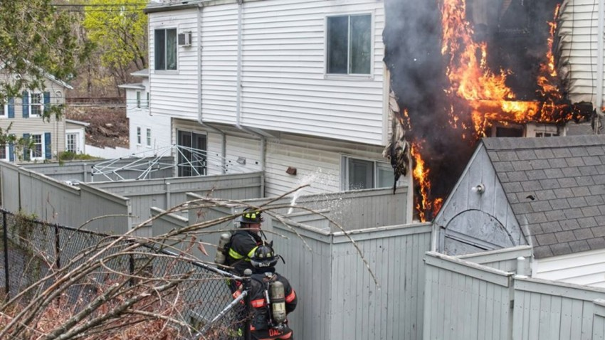flames shoot out from the back of a housing complex in Danbury