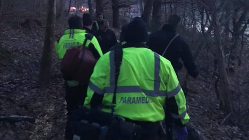rescuers carry victim through the woods