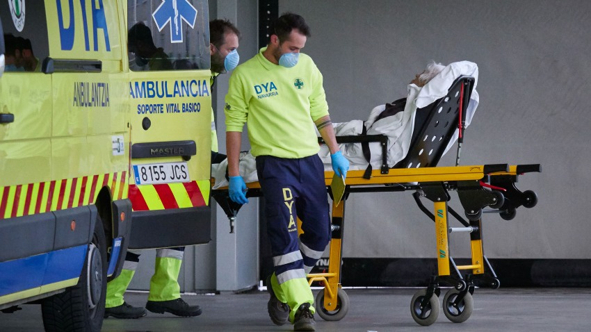 In this April 28, 2020, file photo, members of a DYA Navarra ambulance transfer a patient in the Navarra Hospital Complex during Pandemia COVID-19 in Pamplona, Navarra, Spain.