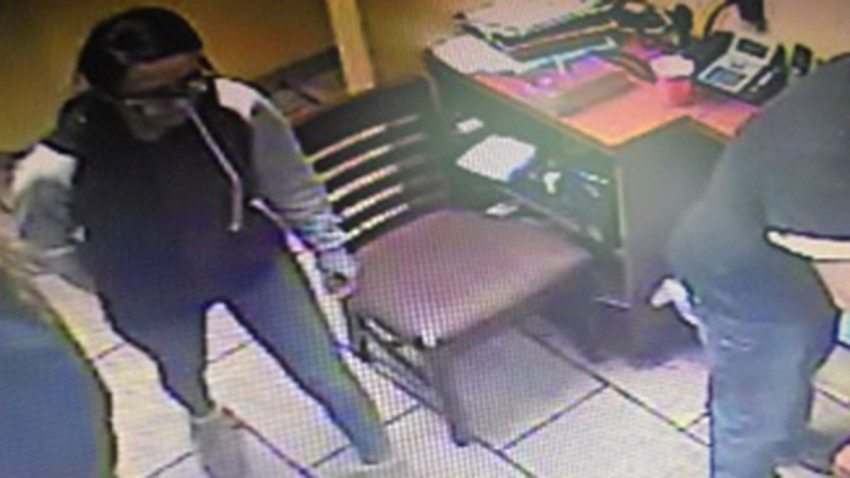 a surveillance image of a woman standing in a Putnam restaurant