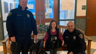 young girl standing with Wethersfield police after donating toys