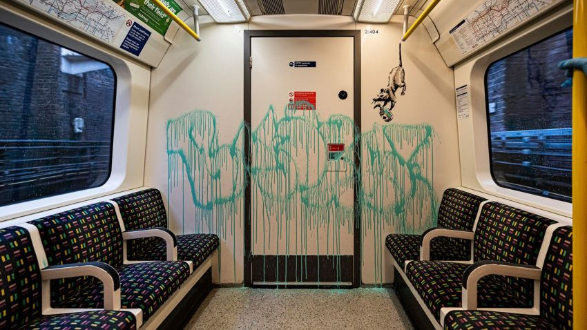 This undated photo issued on Tuesday July 14, 2020 by JBPR, shows Banksy's latest work sprayed on the inside of a London Underground tube carriage. Enigmatic graffiti artist Banksy uploaded a video to social media on Tuesday of what appeared to be him in disguise as a professional cleaner spray painting images of rats on the inside of a London Underground train along with messages about spreading the new coronavirus.