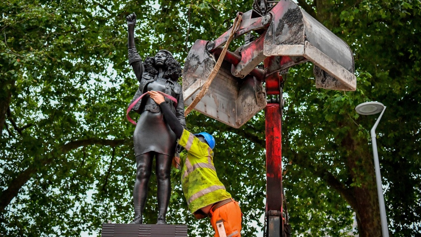 """A contractor uses ropes to secure the statue """"A Surge of Power (Jen Reid) 2020"""" by artist Marc Quinn, which had been installed on the site of the fallen statue of the slave trader Edward Colston, as they prepare to remove and load it into a recycling and skip hire lorry, in Bristol, Thursday, July 16, 2020. The sculpture of protestor Jen Reid was installed without the knowledge or consent of Bristol City Council and was removed by the council 24 hours later."""