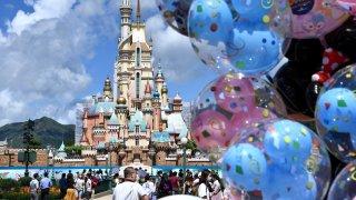 Visitors wearing face masks look at the Castle of Magical Dreams at Hong Kong Disneyland