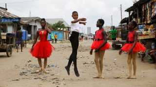 Ballet student Anthony Mmesoma Madu, center, dances in the street as fellow dancers look on in Lagos, Nigeria on Aug. 18, 2020