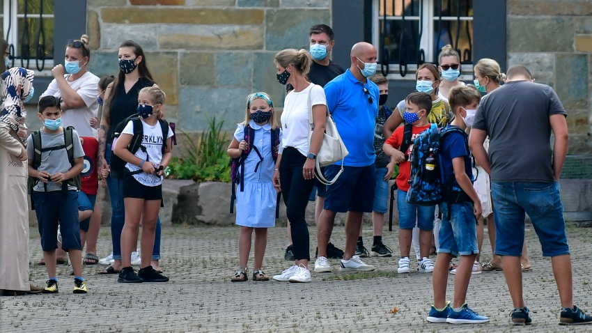 FILE - In this Wednesday, Aug. 12, 2020 file photo, parents wait with children on the schoolyard for the start of their first day at a school in Gelsenkirchen, Germany. Just in time for back-to-school for millions of kids, the World Health Organization on Monday, Aug. 24, 2020 has issued guidance about mask-wearing by children, suggesting in particular that those aged 6 to 11 should wear them too in some cases to help fight the spread of the coronavirus. The WHO recommendations follow upon the widespread belief that children aged under 12 are not considered as likely to propagate the virus as much as adults.
