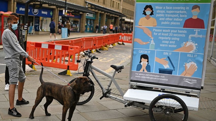 A man wearing a protective face mask restrains his dog beside a promotion funded by Calderdale Council, an ad bike display advising people on how to slow the spread of the coronavirus, in Halifax in northern England on August 9, 2020, as local lockdown restrictions are reimposed due to a spike in cases of the novel coronavirus in the town.