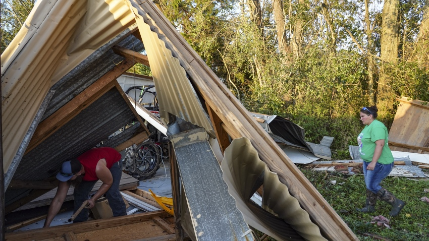 """People clear debris from a damaged garage after Hurricane Laura made landfall in Orange, Texas, U.S., on Thursday, Aug. 27, 2020. Hurricane Laura raked across Louisiana early on Thursday, becoming one of the most powerful storms ever to hit the state with a """"catastrophic storm surge,"""" flash floods and devastating winds that could inflict more than $15 billion in insured losses."""