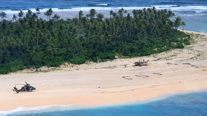 """In this photo provided by the Australian Defence Force, an Australian Army helicopter lands on Pikelot Island in the Federated States of Micronesia, where three men were found, Sunday, Aug. 2, 2020, safe and healthy after missing for three days. The men were missing in the Micronesia archipelago east of the Philippines for nearly three days when their """"SOS"""" sign was spotted by searchers on Australian and U.S. aircraft, the Australian defense department said."""