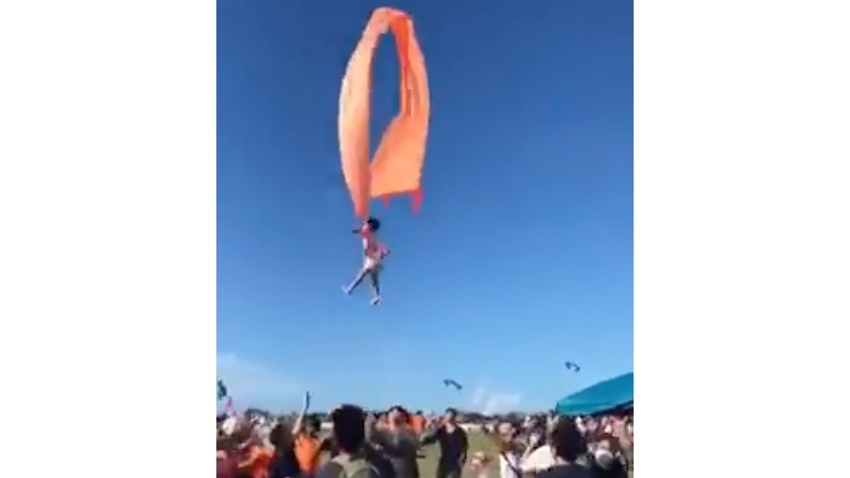 In this image made from video, a 3 year old girl is lifted into the air by a large kite during a kite festival in Hsinchu, northern Taiwan, Sunday, Aug. 30, 2020. The wind slowed down and the girl was safely recovered by adults on the ground.