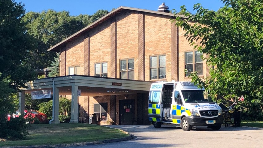 an ambulance sits outside Three Rivers Nursing Home in Norwich