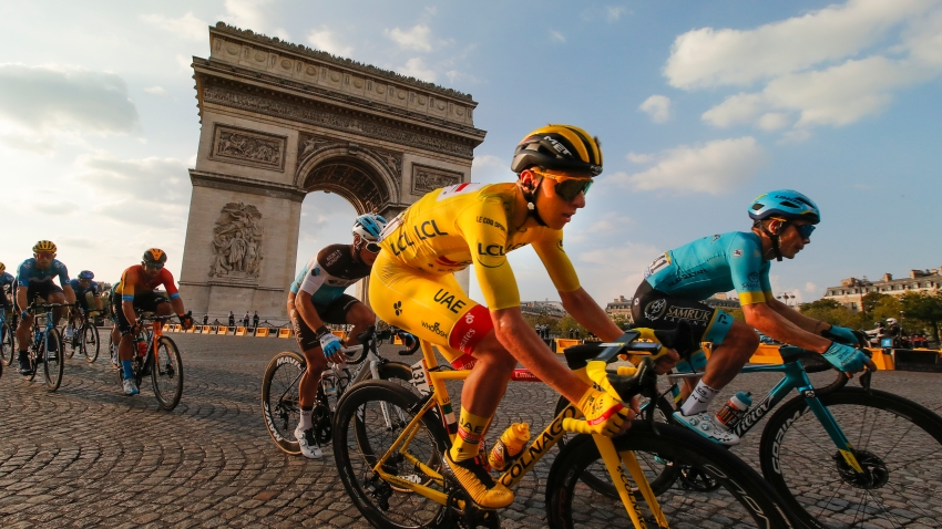 Slovenia's Tadej Pogacar, wearing the overall leader's yellow jersey, rides past the Arc de Triomphe on the Champs-Elysees