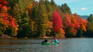 Two people and a dog canoe in Waterbury, Vermont, as the trees change colors in the fall