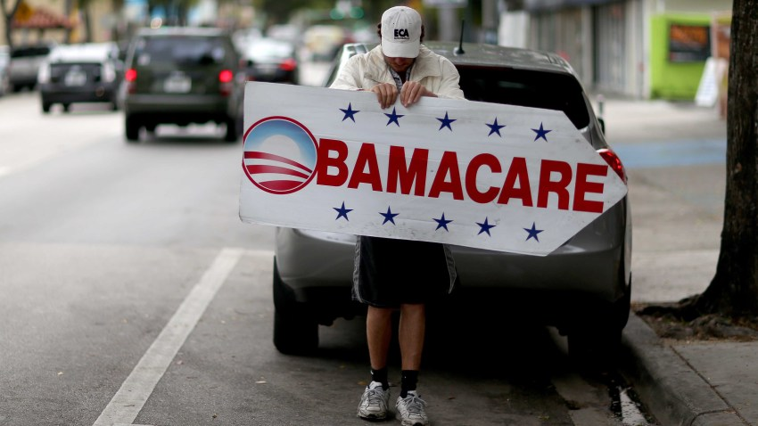 Pedro Rojas holds a sign directing people to an insurance company where they can sign up for the Affordable Care Act, also known as Obamacare