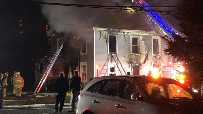 fire ladders extended over a fire-damaged house
