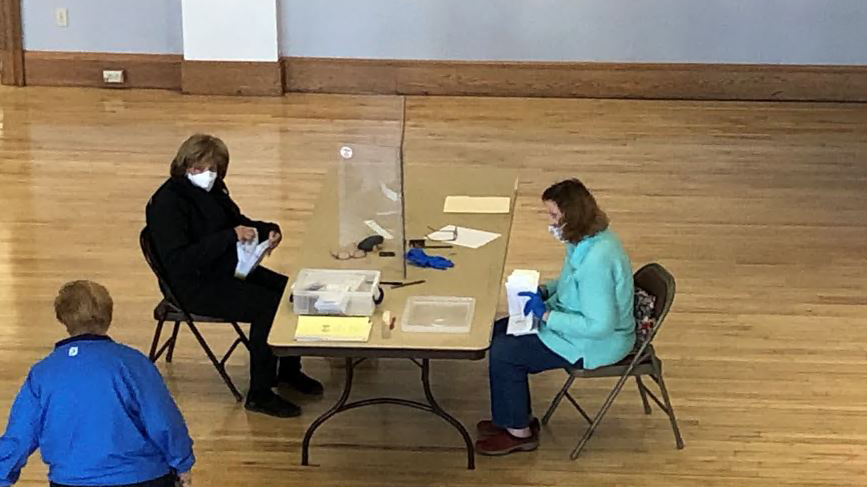 workers sit divided by plexiglass, counting absentee ballots