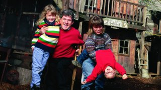 Matt Roloff (foreground, second from left) and wife Amy (foreground, second from right) with children Molly (foreground, left) and Jacob (foreground, right) playing on the playground Matt constructed complete w. Old West Town and a pirates ship.