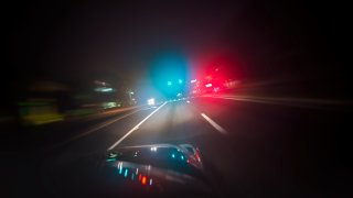Car driving down road with red and blue lights
