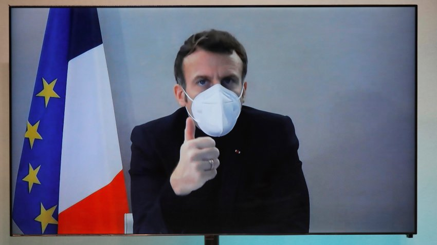 French President Emmanuel Macron is seen on a screen as he attends by video conference a round table for the National Humanitarian Conference (NHC), taken at the Foreign Ministry in Paris, Thursday, Dec. 17, 2020. French President Emmanuel Macron tested positive for COVID-19 Thursday following a week in which he met with numerous European leaders. The French and Spanish prime ministers and EU Council president were among many top officials self-isolating because they had recent contact with him.
