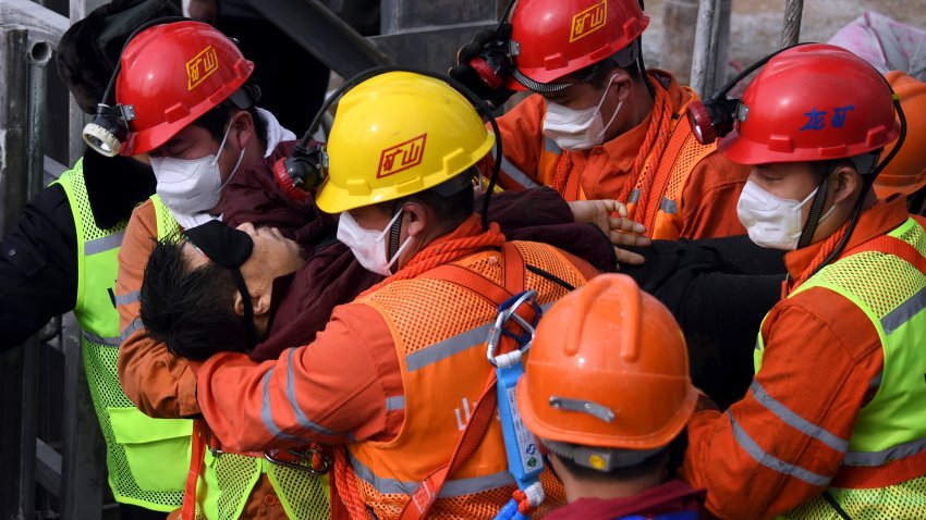 rescuers carry a miner who was trapped in a mine to an ambulance