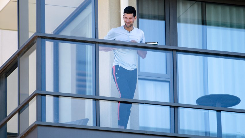 Serbia's Novak Djokovic stands on the balcony at his accommodation in Adelaide, Australia, Tuesday, Jan. 19, 2021. Australian Open tournament director Craig Tiley defended Djokovic for appealing to Australian Open organizers to ease restrictions so players could move to private residences with tennis courts.
