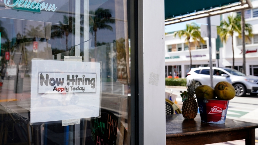 "A ""Now Hiring,"" sign is shown in the window of a restaurant, Thursday, Jan. 7, 2021, in Miami Beach, Florida. America's employers likely cut back on hiring last month, and may have even shed jobs, as the economy suffers from a resurgent virus that has caused many consumers to cut back on spending and states and cities to reimpose business restrictions."